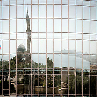 Baku, Azerbaijan, 26 July 2012<br /> The city of Baku is reflected on the windows of the Flames towers.<br /> Baku is the capital and largest city of Azerbaijan, as well as the largest city on the Caspian Sea and of the Caucasus region. It is located on the southern shore of the Absheron Peninsula, which projects into the Caspian Sea. <br /> The city consists of two principal parts: the downtown and the old Inner City (21.5 ha). <br /> Baku's urban population at the beginning of 2009 was estimated at just over two million people. Officially, about 25 percent of all inhabitants of the country live in the metropolitan city area of Baku.<br /> Photo: Ezequiel Scagnetti