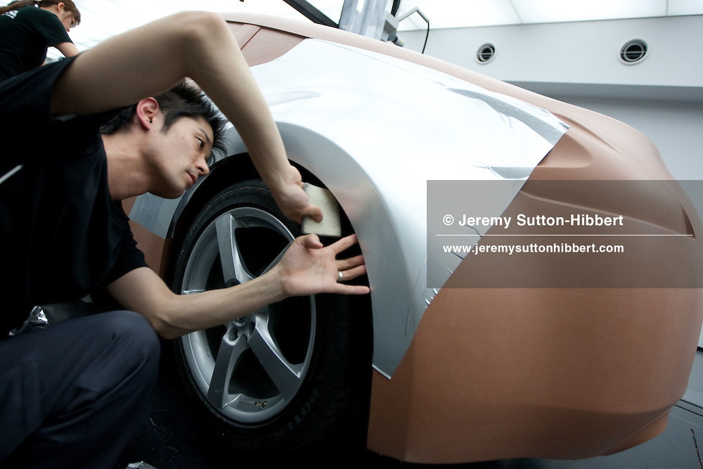 Clay modellers begin smoothing Dynoc film onto a clay production model of the Nissan 'Fairlady Z' car model, to imitate a metalic finish on the car, at the Nissan Design Centre, Atsugi, Japan, on Friday 26th March 2010.