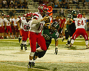 Mustang quarterback Chandler Garrett escapes a tackle from Norman North's Trevor Magee during Thursday night's game at Harve Collins Field - Nicholas Rutledge / The Transcript (Published on Friday, October 10, 2014)