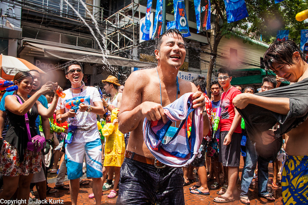 """13 APRIL 2013 - BANGKOK, THAILAND:  A Japanese tourist is deluged with water during a Songkran water fight on Khao San Road, which is Bangkok's """"backpacker"""" district, during Songkran celebrations in the Thai capital. Songkran is celebrated in Thailand as the traditional New Year's Day from 13 to 16 April. The date of the festival was originally set by astrological calculation, but it is now fixed. If the days fall on a weekend, the missed days are taken on the weekdays immediately following. Songkran is in the hottest time of the year in Thailand, at the end of the dry season and provides an excuse for people to cool off in friendly water fights that take place throughout the country. Songkran has been a national holiday since 1940, when Thailand moved the first day of the year to January 1.   PHOTO BY JACK KURTZ"""