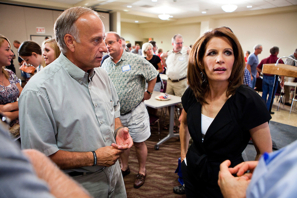 Rep. Steve King (R-IA), left, and Republican presidential candidate Rep. Michele Bachmann (R-MN) talk with aides after a campaign stop at the Calhoun County Republican Party dinner on Monday, August 8, 2011 in Rockwell City, IA.