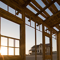 Africa, Namibia, Kolmanskop, Morning sun lights broken windows inside decaying building in ghost town of abandoned diamond mining town