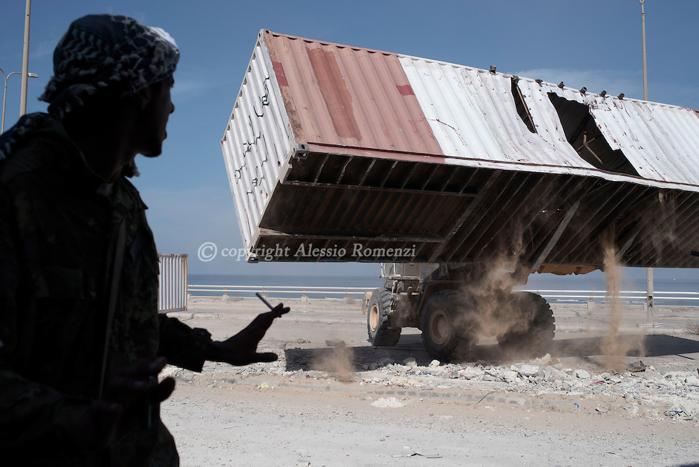 Libya, Sirte: A fighter of the Libyan forces affiliated to the Tripoli government gestures as a bulldozer moves a container in order to build a barricade Al Jiza neighbourhood on the frontline with ISIS in Sirte on November 24, 2016.  Alessio Romenzi