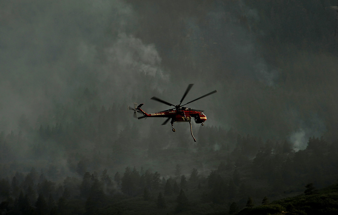 A helicopter prepares to drop water on the fire as firefighters continued to battle the blaze that burned into the evening hours in Waldo Canyon, Colorado, on the U.S. Air Force Academy June 27, 2012. — © Jeremy Lock/USAF