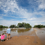 DEARFIELD, CO - SEPTEMBER 14: Allison Wold of Denver, Colorado and her nephew, Jack Wold, take in a flooded ranch home with John Brinckerhoff, also of Denver, near Dearfield, Co. They were trying to cross County Road 87 to get to some family property but couldn't because of the flooding. Heavy rains for the better part of week fueled widespread flooding in numerous Colorado towns on September 14, 2013. (Photo by Marc Piscotty/ © 2013)