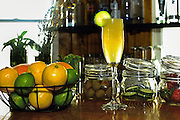 Food photographer Keith Carter Katy Texas Photography of a frosty yellow beverage top off with a cucumber in a flute Glass surround condiments lemon, lime, orange, olives, cucumbers, strawberries