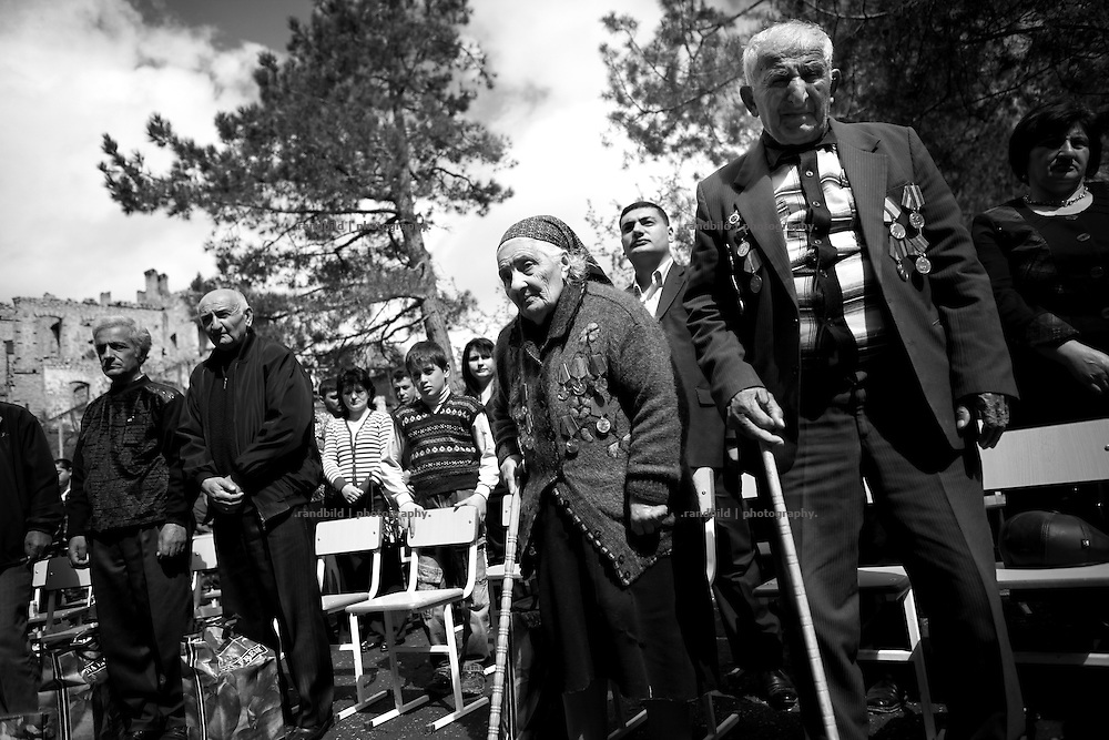 """Two very old World War II veterans during a celebration event. This image is part of the photoproject """"The Twentieth Spring"""", a portrait of caucasian town Shushi 20 years after its so called """"Liberation"""" by armenian fighters. In its more than two centuries old history Shushi was ruled by different powers like armeniens, persians, russian or aseris. In 1991 a fierce battle for Karabakhs independence from Azerbaijan began. During the breakdown of Sowjet Union armenians didn´t want to stay within the Republic of Azerbaijan anymore. 1992 armenians manage to takeover """"ancient armenian Shushi"""" and pushed out remained aseris forces which had operate a rocket base there. Since then Shushi became an """"armenian town"""" again. Today, 20 yeras after statement of Karabakhs independence Shushi tries to find it´s opportunities for it´s future. The less populated town is still affected by devastation and ruins by it´s violent history. Life is mostly a daily struggle for the inhabitants to get expenses covered, caused by a lack of jobs and almost no perspective for a sustainable economic development. Shushi depends on donations by diaspora armenians. On the other hand those donations have made it possible to rebuild a cultural centre, recover new asphalt roads and other infrastructure. 20 years after Shushis fall into armenian hands Babies get born and people won´t never be under aseris rule again. The bloody early 1990´s civil war has moved into the trenches of the frontline 20 kilometer away from Shushi where it stuck since 1994. The karabakh conflict is still not solved and could turn to an open war every day. Nonetheless life goes on on the south caucasian rocky tip above mountainious region of Karabakh where Shushi enthrones ever since centuries."""