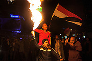 Egyptian youths celebrate the news that Egyptian President Hosni Mubarak had stepped down by burning aerosols and waving flags February 11, 2011 in the Mohandiseen District of Cairo, Egypt. (Photo by Scott Nelson)