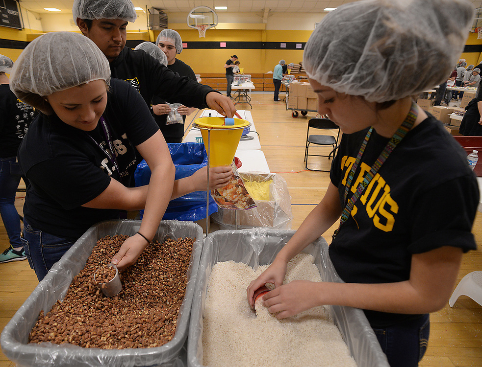apl041217d/ASECTION/pierre-louis/JOURNAL 041217<br /> St. Pius X High School sophomores from left Hailee Eldredge,, 16, Matt Row,, 15 and Olivia Chavez,,16,  fill food packets during the 9th Annual Making a difference against Hunger&quot; held at the cathlolic school gym. More than 1,200 students from local parochial schools fill more than 200,000 packets that will be delivered to food pantries  .Photographed on Wednesday April 12, 2017. .Adolphe Pierre-Louis/JOURNAL