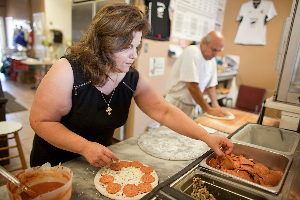 London, Ontario ---10-09-24--- Kyriaki Antoniou makes a pizza at Cyprus Pizza in London, Ontario which she co-owns with her brother-in-law Tony, right. Kyriaki recently underwent a new weight loss procedure which inserts a balloon into the stomach. Since the procedure a month ago she has lost over 20 pounds.<br /> GEOFF ROBINS The Globe and Mail