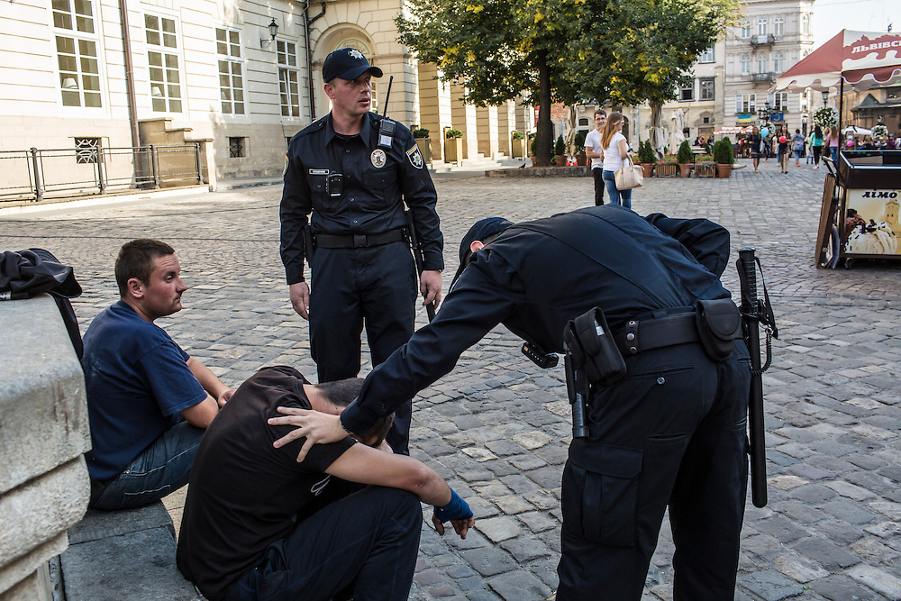 LVIV, UKRAINE - SEPTEMBER 15, 2015: Vasil Spodayk, 33, and Roman Katalakh, 22, right, both members of the new police, check on two men who appeared to be intoxicated in Market Square, the tourist-friendly central square in Lviv, Ukraine. In an effort to reform the notoriously corrupt Ukrainian police force, an entirely new force has been established in several cities, including Kiev and Lviv, with a primary focus on patrolling the streets. CREDIT: Brendan Hoffman for The New York Times