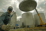 Anthony Travis of Cape Girardo, Mo. guides the lid of a 730,000-gallon tank as it is lifted into place Friday, Sept. 26, 2003, while working for Winbco Tank Company of Ottumwa. Big River Resources built the plant with expansion in mind, and left room for two more of the giant tanks that will increase the plant's productivity.