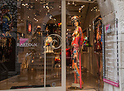 A crisp view of the colorful mannequin; a dimmed view of the photographer. Saint Paul village, France.