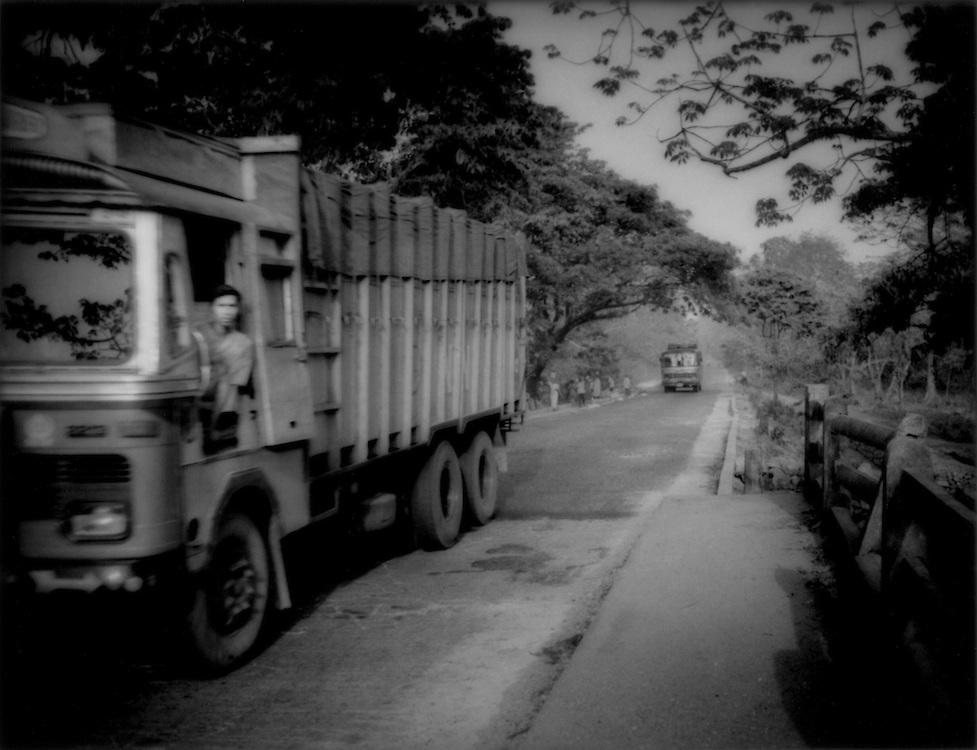 Heavy truck traffic on the main road outside Jaldapara Wildlife Sanctuary , West Bengal, India. .