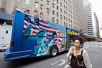 woman walks past tourist bus in New York October 2008