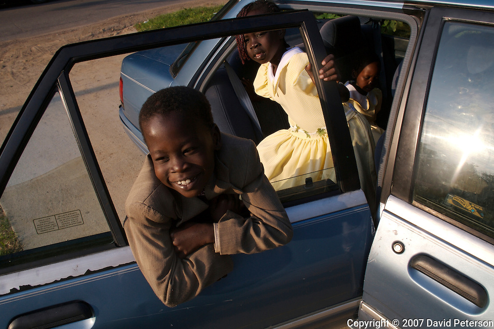 Dressed in their finest, Kolmut Mai, 8, and his sister Buk, 6, wait for the rest of their family before heading to the Capitol Hill Lutheran Church in Des Moines, Iowa.  Beginning in the summer of 1992 Sudanese refugees began arriving in Des Moines through the efforts of the Lutheran Immigration and Refugee Services.  They now number over 800 in Iowa.  The Mai family arrived in 1998, seeking freedom from a war and religious persecution perpetrated by Muslims.  Just two years ago they moved into their new home in a better and safer neighborhood.  But  home for the Mai's is not just the four walls of a house, but America itself, where they have been able to build a new life.
