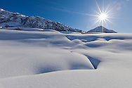 The late winter sun rises high enough in the sky to illuminate the deep snow in the Talkeetna Mountains of Hatcher Pass in Southcentral Alaska. Afternoon. Winter.