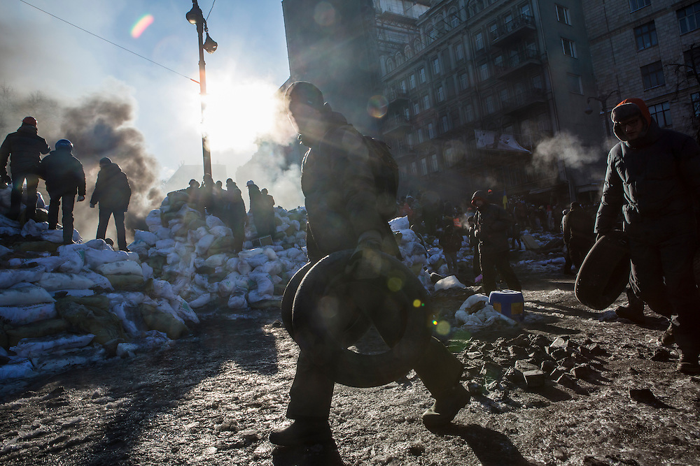 KIEV, UKRAINE - JANUARY 24: Anti-government protesters carry tires to fortify the front lines of their occuption near the Dynamo stadium on January 24, 2014 in Kiev, Ukraine. After two months of primarily peaceful anti-government protests in the city center, new laws meant to end the protest movement have sparked violent clashes in recent days. (Photo by Brendan Hoffman/Getty Images) *** Local Caption ***