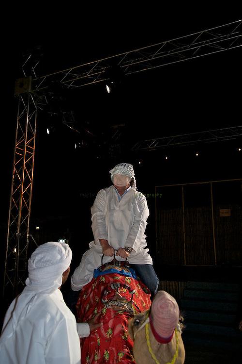 Andy Borg reitet zu Beginn des Konzertabends auf einem Kamel in das Wuestencamp ein, gekleidet in einer Kandura, dem Gewand der emiratischen Maenner.