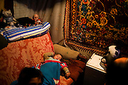 A child sleeps in the home of a Roma family in the New Belgrade Roma settlement of Belville.