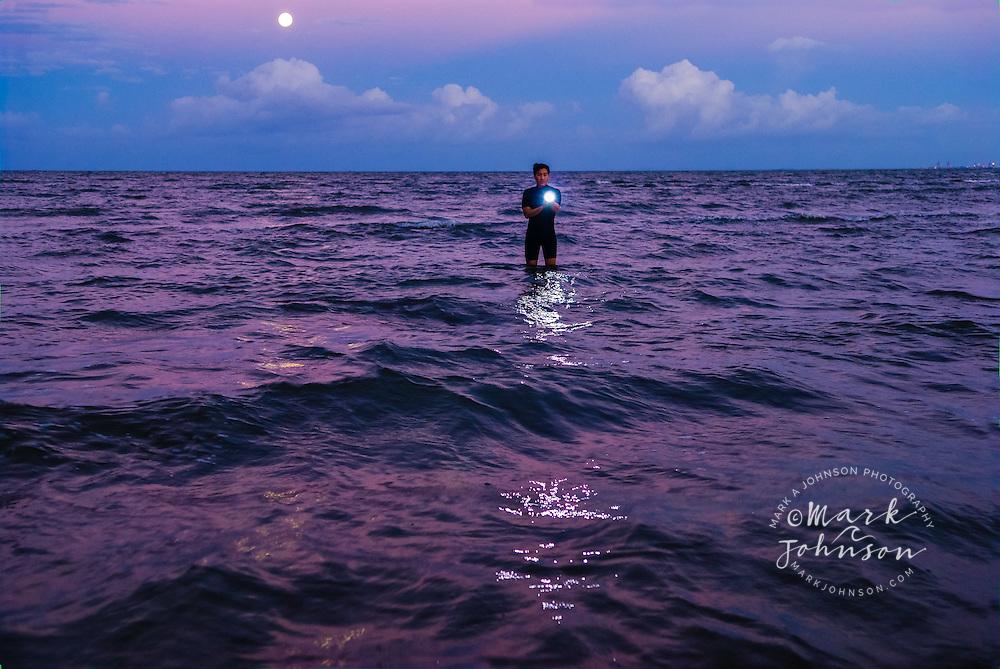 Brisbane, Australia --- Man with Flashlight Standing in Ocean