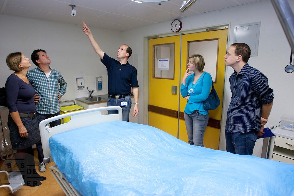Bezoekers krijgen uitleg over de isolatieruimte van het calamiteitenhospitaal, waar pati&euml;nten met besmettelijke ziekten behandeld worden. Ter gelegenheid van haar tienjarig bestaan houdt het UMC Utrecht op 9 oktober een open dag. Bezoekers kunnen een kijkje nemen achter de schermen en ook het calamiteitenhospitaal bezoeken.<br /> <br /> Visitors are listening during a tour at the trauma and emergency hospital. The UMC Utrecht is celebrating its 10th anniversary by giving an open house to the public.