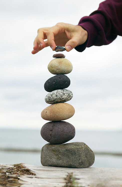 Hand carefully stacking stones on a log.