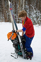 Russell Laman putting on his backpack while hiking in the White Mountains, New Hampshire.