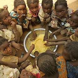 Children eat lunch, often their only meal of the day after school in the  village of Intedeyne March 15, 2007.    Food is provided by Oxfam in an effort to encourage the children to attend school. the challenge to educate children in Mali still exists and particularly for girls. Female literacy rates never reach even 50 percent of male literacy rates. Mali has the highest percentage of people living below the poverty line in any country in the world. Ninety percent of Malians survive on less than two dollars a day.