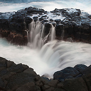 Pacific Ocean waves crash into a narrow inlet in an old lava flow near Princeville on the Hawaiian island of Kauai.