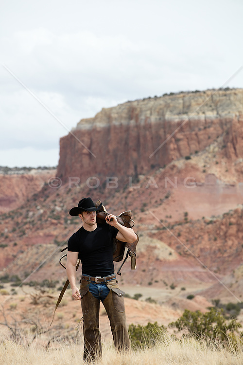 cowboy holding a saddle on a mountain range