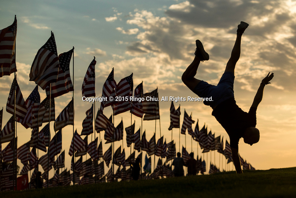 A man handstands amongst 3,000 US flags are displayed at Pepperdine University to mark the 14th anniversary of the 9/11 terror attack, September 10, 2015 in Malibu, California.  Photo by Ringo Chiu/PHOTOFORMULA.com)