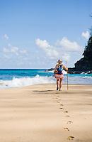 Female hiker walking toward the surf on  Hanakapiai Beach.  The Na Pali Coast of Kauai, Hawaii.