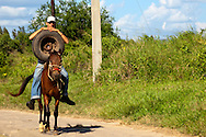 Man and tire on a horse in Pinar del Rio, Cuba.