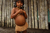Viriunaveteri, Venezuela. A Yanomami girl watching a tribal dance. .The village of Viriunaveteri consists of 15 huts around a muddy square. It's situated in the Venezuelan Amazone several days by boat from the nearest town. This community on the banks of the Casiquiare is one of the few Yanomami villages that actually has some contact with the outside world. Most other tribes live deeper in the jungle.