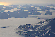 Aerial view over Isfjorden of Nansenbreen glacier covered in snow in April on flight from Longyearbyen to Ny-Alesund; Svalbard, Norway.