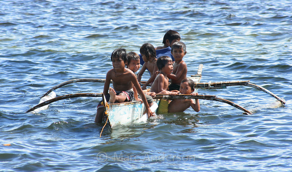 Young children playing in a small boat, Olango Island, Cebu, Philipines