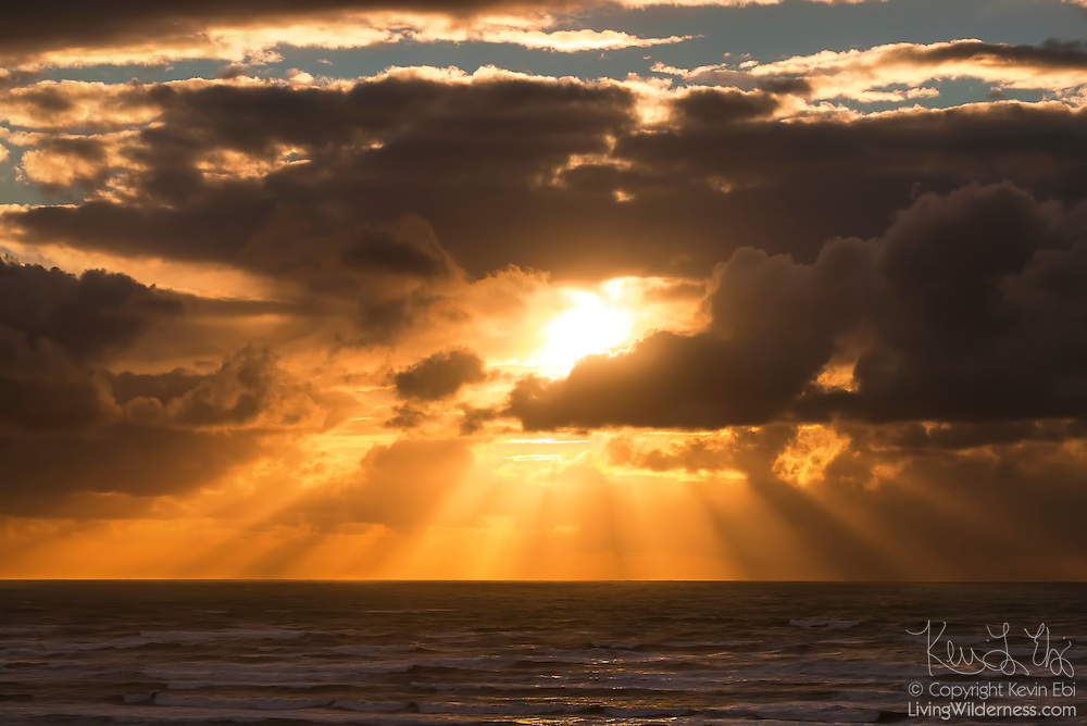 Vibrant shafts of light, called crepuscular rays, radiate from the sun as it sets over the Pacific Ocean. The clouds surrounding the sun cast their shadows over the ocean, forming the beams. This image was captured in Pacific Beach, Washington.