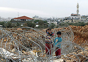 Palestinian children Mousa and Diana Darwish stand amongst the barbed wire trench which separates their home near the Palestinian city of Bethlehem Nov.13,2002 from the rest of Bethlehem. The barbed wire trench separates access to the Israeli Jerusalem disputed neighborhood of Gilo.A security fence will replace the barbed wire.(Photo by Heidi Levine/Sipa Press).