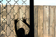 A Palestinian boy outside the entrance of the Armer family play in the window and the entrance of their home which has been isolated from their village of Masha in the Occupied West Bank Oct.28,2003.A 8 meter high concrete wall together with an electrical fence has cut this family off from their relatiand their village .Their  home is now on the Israeli side of the Wall.There home is adjascent to the Israeli Jewish settlement of ElkanaThe wall is part of a combination of fences, razor wires and trenches that Israel is building between Israel and the Palestinian territories Thursday Oct. 23, 2003. Israel says it is building it to keep out Palestinian suicide bombers and gunmen. The Palestinians say Israel is grabbing land, unilaterally drawing a border and making it impossible to establish a viable Palestinian state. (Photo by Heidi Levine/Sipa Press)