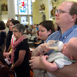 2 AUG. 2015 -- ST. LOUIS -- Michael Kress (right), Director of Mission Advancement at Most Holy Trinity Catholic Church, joins other worshipers gathered for Mass Mob III at Sts. Teresa and Bridget Catholic Parish in St. Louis Sunday, Aug. 2, 2015. The event brings Catholics from across the Archdiocese of St. Louis to worship at historic, urban parishes.<br /> <br /> Photo by Sid Hastings.