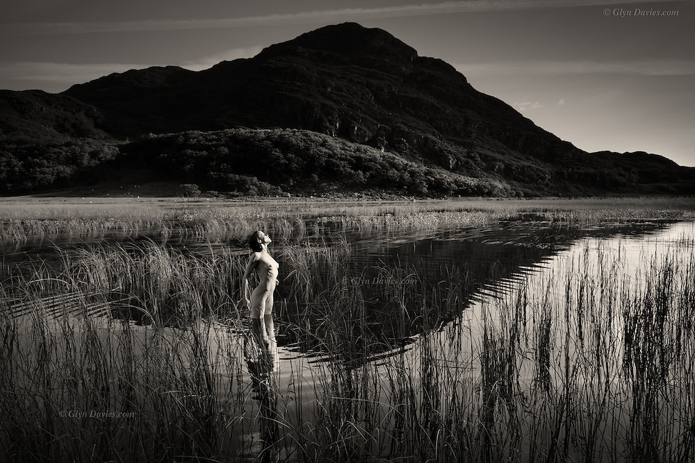 &quot;In this lonely Welsh valley nestles a large but often calm lake. Reeds puncture the glassy smooth surface and there is silence, apart from the occasional bleating of Welsh mountain sheep, or the call of a Raven over the hillsides. This woman was so bird-like in stature, so graceful and so slim, that she reminded me of the Heron which often frequents this place. She delicately pointed each foot into the lake so as not to overly disturb it's surface and even the act of doing this mimicked the beautiful creature. &nbsp;She turned to face the light, her front feeling the gentle warmth of the afternoon sun, as the cold water clasped her legs, and she stood motionless, embracing the sensations as I shot a few frames of this human wader.&quot;<br /> <br /> <br /> _____________________________<br /> <br /> <br /> &quot;Landscape Figures&quot; explores the relationship between organic human figures and a notional 'wild landscape'. <br /> <br /> &ldquo;Although the nude is vital to the project and integral within the images, the images are not just &lsquo;nudes&rsquo; &ndash; they are landscapes and stories. In a way they are just simple, beautiful, dreamlike visual questions&rdquo;.
