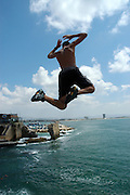 Israel, Acre, young boy jumping off the walls of the old city into the Mediterranean sea