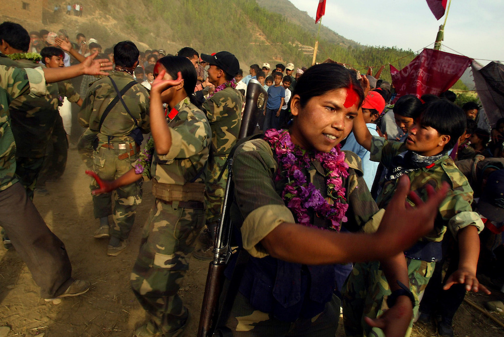 Troops from the 2nd Battalion dance alongside villagers after descending from the mountains in to the valley to take part in a cultural program and remembrance ceremony in the village of Kholagaun, in the Maoist heartland of Nepal Thursday April 22, 2004.  In the mountains of Nepal, one of the world's last full-blown Maoist revolutions is thriving/forging ahead/gaining ground. The doctrines of Mao, the Chinese communist leader who believed in communism via an empowered peasantry, have found new life in the farm fields of this Himalayan kingdom. The rebels contend their revolution _ which has cost more than 9,500 lives _ is only possible through the barrel of a gun.
