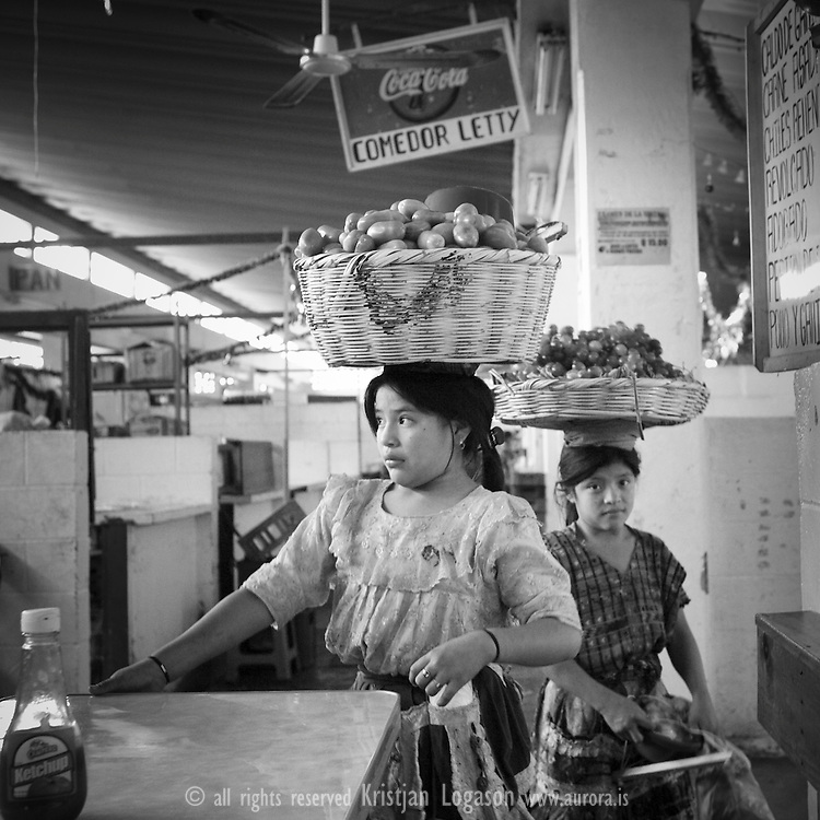 Young girls selling vegetables and fruits at the market in Antigua Guatemala