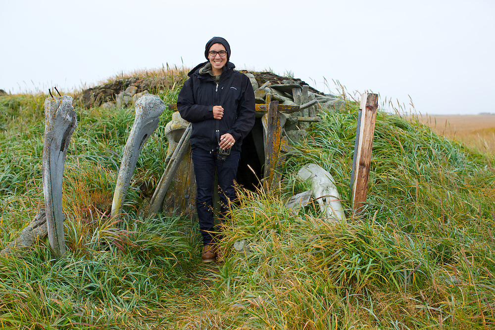POINT HOPE, ALASKA - 2013: Brian Adams in front of a sod house in old Point Hope, Alaska.