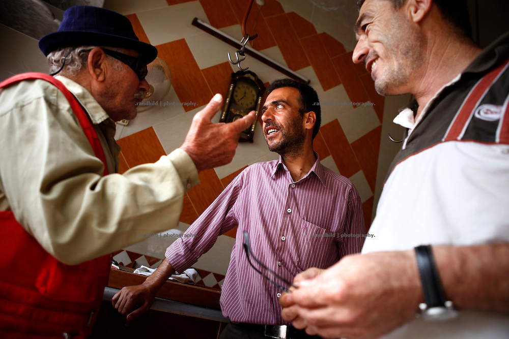 Some men chatting in a butchery in Koreen.<br /> _ _ _ <br /> Idlib Interim - Challenging life without central government in the village of Koreen (Idlib Province, Syria)<br /> Koreen joint the syrian uprisung to ouster president Bashar al-Assad at a very early stage in 2011. It has been scene of Army attacks and heavy shelling since 2012. In the course of the fightings the village of a few thousend inhabitants was almost abandoned as barrel bomb campaings commited by the regime pounded Koreen. But since regime forces retreated to few bases remaining in Idlib province people returned home to establish a new and almost unregulated economic, social and community life. The regimes power has no affect and can&acute;t reach them anymore. On the other hand a new government isn&acute;t established yet and not in sight at all. Koreen is free to make its way.