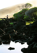 A boy scampers from the rocks as the tide recedes near Punalu'u on the Big Island of Hawaii.