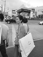 Japanese tourist carrying a 'Prada' shopping bag in Tumon, Guam, on Saturday, Mar. 10, 2007.  Sometimes known as 'America in Asia', Guam is a popular destination for Japanese tourists ( accounting for approx 90% of the island's visitors) with average visitor numbers from Japan approaching 1million.  The island, a 3.5 hour flight from Japan, has more than 20 large hotels and numerous duty-free shopping malls catering to the Japanese tourists predilection for designer brand name goods, as well as golfing and other water based entertainment features. In 2007-2008 US military personal currently stationed in the Japanese Okinawan Islands will relocate their bases and operations  to Guam, helping to stabilise the island's economy which suffered after tourism decreased in recent years due to a  fear of flying by Japanese post 9-11 World Trade Centre disaster, a 2003 typhoon and the SARS disease outbreak in Asia.
