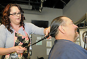 gbs121213d/ASEC -- John Morelock has his braided, long hair cut off by his daughter, Audrey Morelock, at the Hair Addict salon on Thursday, December 12, 2013. The braided locks with be donated to Pantene Beautiful Lengths which gives free wigs to adult cancer victims.(Greg Sorber/Albuquerque Journal)